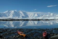 在镜子蓝色海湾的南极洲橙色和红色皮船 免版税库存照片