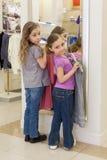 在镜子附近的两个逗人喜爱的女孩在商店试穿衣裳 库存照片