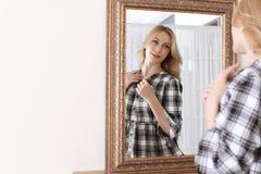 在镜子附近的年轻美丽的妇女 库存照片