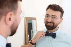 在镜子附近的年轻英俊的人 库存照片