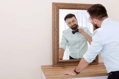 在镜子附近的年轻英俊的人 库存图片