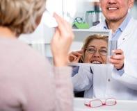 在镜子附近的正面女性白肤金发的买的眼镜 免版税库存照片