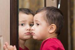 在镜子附近的男孩 免版税图库摄影