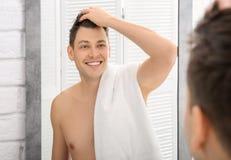 在镜子附近的英俊的被刮的人 免版税库存照片