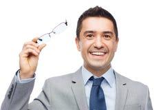 在镜片和衣服的愉快的微笑的商人 库存照片
