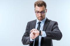 在镜片的检查在手表的年轻商人画象时间 免版税库存图片