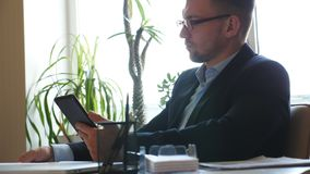 在镜片的英俊的商人分析关于一平板电脑的统计数字信息在办公室 年轻企业家 股票视频