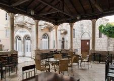 在镭古城的正方形的老木和石门廊 库存照片