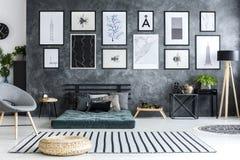 在镶边地毯的蒲团在与画廊的灰色客厅内部  库存图片