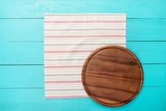 在镶边桌布的布朗圆的切板 蓝色木背景在餐馆 复制空间 嘲笑 图库摄影