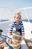 在镶边海洋衬衣的滑稽的孩子 小船的小水手 ?? o 旅途发现 免版税库存图片