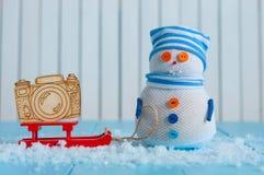 在镶边盖帽的手工制造雪人有红色雪撬的和 免版税库存图片