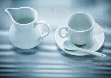 在镶边背景的白色陶瓷杯子茶碟茶匙盛奶油小壶 库存图片