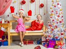 在长凳坐盖帽的一个女孩,并且圣诞老人手套,有笑的另一个女孩从袋子出来 免版税库存照片