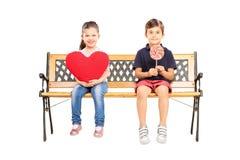 在长凳安装的两个孩子拿着大红色心脏和棒棒糖 免版税库存照片