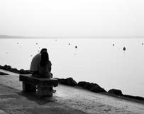 在长凳安装的恋人由由后照的湖边 免版税库存图片