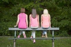 在长凳安装的Hree年轻女性朋友,户外 库存图片