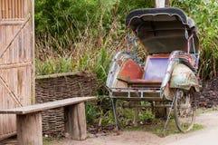 在长凳旁边的人力车 免版税库存照片