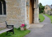 在长凳旁边被看见的一个老,中世纪教会的外视图在公墓附近 库存照片
