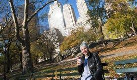 年轻在长凳的人微笑的和饮用的咖啡在中央公园N 免版税图库摄影
