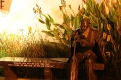 在长凳的古铜色经验丰富的雕象在晚上 图库摄影