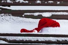 在长凳的圣诞老人红色帽子与雪 免版税库存照片