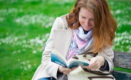 在长凳的女孩读书 免版税库存图片