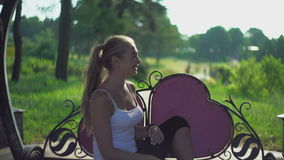 在长凳的女孩跳舞用他的手和笑 股票录像
