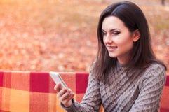 在长凳的妇女键入的消息 免版税库存照片