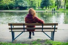 在长凳的妇女sittng由一个池塘在公园 免版税库存照片