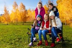在长凳的孩子与电话 库存照片