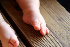在长凳的小的赤裸婴孩` s腿 免版税库存图片