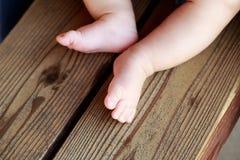 在长凳的小的赤裸婴孩` s腿 库存照片