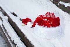 在长凳的特写镜头圣诞老人红色帽子与雪 免版税库存图片