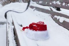 在长凳的红色圣诞老人帽子与雪 库存图片