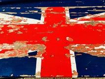 在长凳的老被风化的英国国旗旗子 免版税库存图片