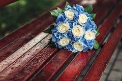 在长凳的蓝色婚礼花束 免版税库存图片