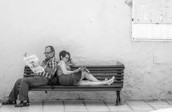 在长凳的读书报纸 库存图片