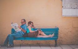 在长凳的读书报纸 免版税库存图片