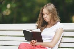 在长凳的年轻十几岁的女孩阅读书 免版税库存图片
