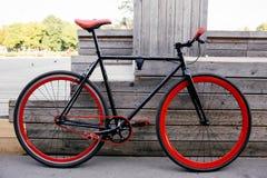 在长凳附近停放的红色bycicle在公园 免版税图库摄影