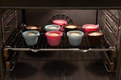 在长大在烤箱的ccolorful硅树脂模子的松饼 杯形蛋糕,面包店 关闭 免版税库存图片
