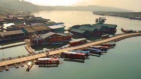 在长尾巴小船和木筏以后日出在木船坞旁边 库存照片