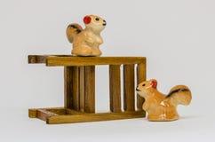 在长木凳的灰鼠Cerimic在公园 免版税库存图片