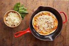在长柄浅锅的煮熟的无盐干酪和火腿薄饼 库存图片