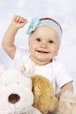 在长毛绒玩具中的愉快的矮小的女婴 免版税库存照片