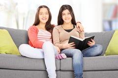 在长沙发供以座位的两个十几岁的女孩摆在 库存照片
