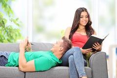 在长沙发在家供以座位的夫妇放松 免版税库存照片