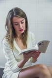 在长沙发在家,冬天、舒适、休闲和人概念的愉快的少妇读书故事书 免版税库存图片