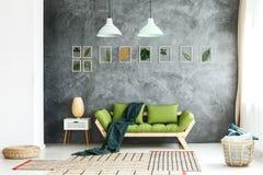 在长沙发投掷的黑暗的毯子 免版税图库摄影